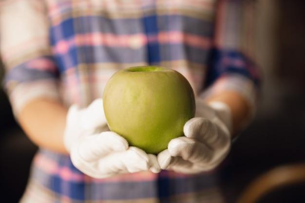 Feche de mãos femininas em luvas segurando maçã verde, comida saudável, frutas. dieta nutricional orgânica, produto natural e fresco cheio de vitaminas. preparando, propondo alguém. copyspace.