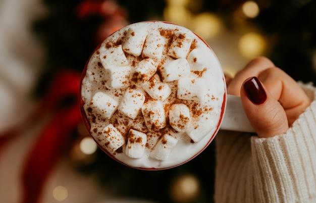 Feche de mãos femininas segurando uma caneca branca com chocolate quente, chá ou café e marshmallow. conceito de época de inverno e natal.