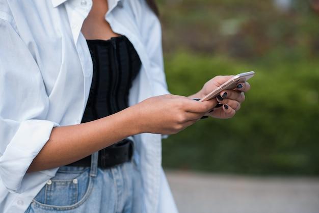 Feche de mãos femininas usando um smartphone.
