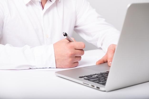 Feche de mãos masculinas, digitando no teclado do laptop enquanto trabalhava na mesa branca.
