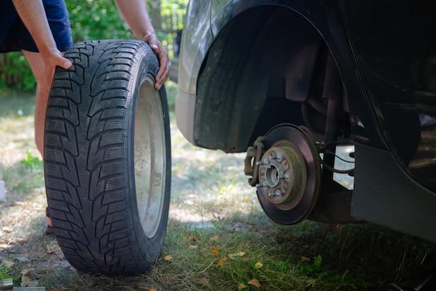 Feche de mãos masculinas, mudando o pneu do carro lá fora. substituindo o pneu do veículo quebrado.