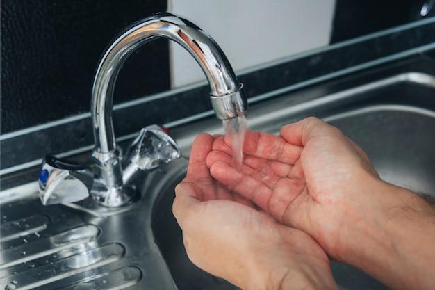 Feche de mãos masculinas sendo lavadas em uma pia de metal. um conjunto de água na palma da mão para lavar o rosto. procedimento higiênico matinal. prevenção de vírus e doenças. remoção de micróbios.