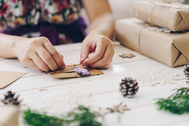 Feche de mãos segurando a caixa de presente de embrulho e cartão de natal na mesa de madeira com decoração de natal.