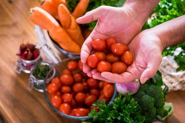 Feche de mãos segurando tomates cereja frescos e de cor vermelha e vários vegetais misturados em cof de fundo.