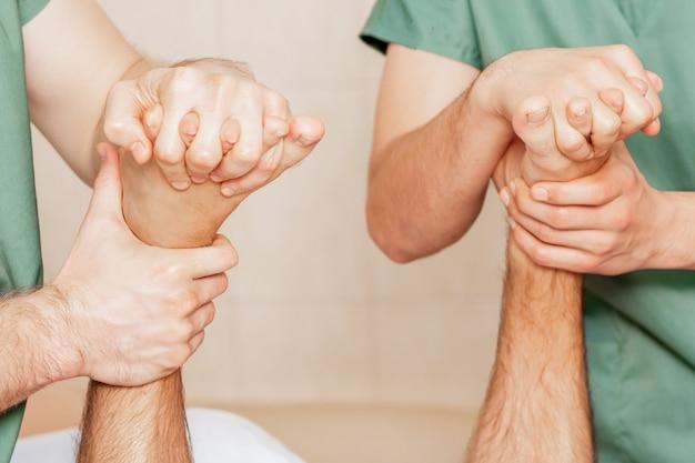 Feche de massagem dos dedos do pé do homem pelas mãos de dois massagistas.