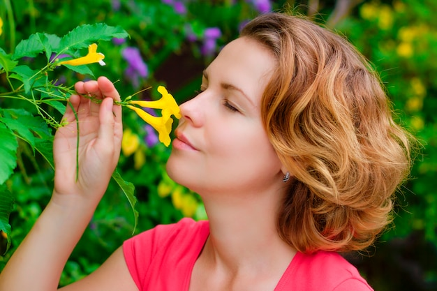 Feche de menina bonita, bela jovem bonita cheirando, cheirando, inala o aroma, apreciando flores frescas de primavera amarelo no jardim com os olhos fechados. flores, flores, natureza, conceito de flora.