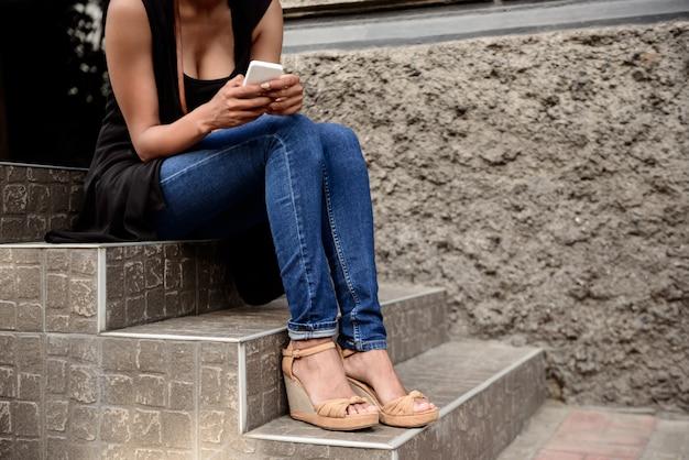 Feche de menina em sapatos, sentado na escada.