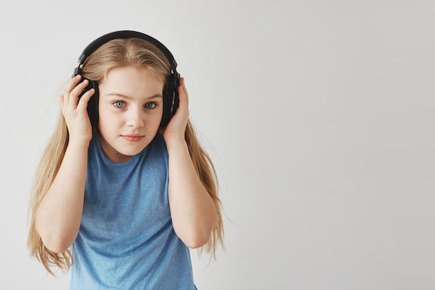 Feche de menina feliz com cabelos loiros na camiseta azul segurando fones de ouvido com as mãos, ouvindo atentamente o texto de audição na escola.