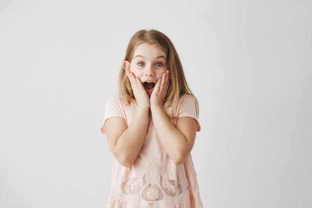 Feche de menina loira bonitinha com olhos azuis em camiseta rosa olhando camer, segurando as mãos nas bochechas com expressão animada.