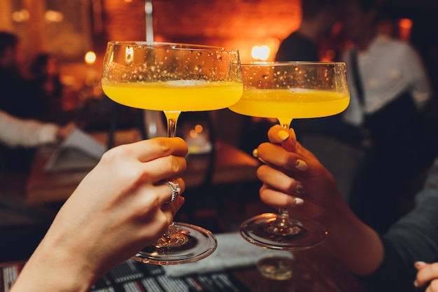 Feche de meninas a beber cocktails em boate. as meninas se divertindo, torcendo e bebendo cocktails frios, desfrutando de amizade juntos no bar, close-up vista nas mãos.