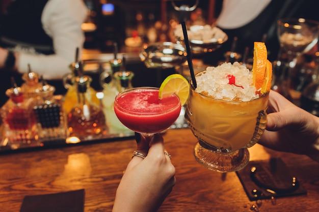Feche de meninas a beber cocktails em boate. as meninas se divertindo, torcendo e bebendo cocktails frios, desfrutando de amizade juntos no bar, fecham a vista nas mãos.