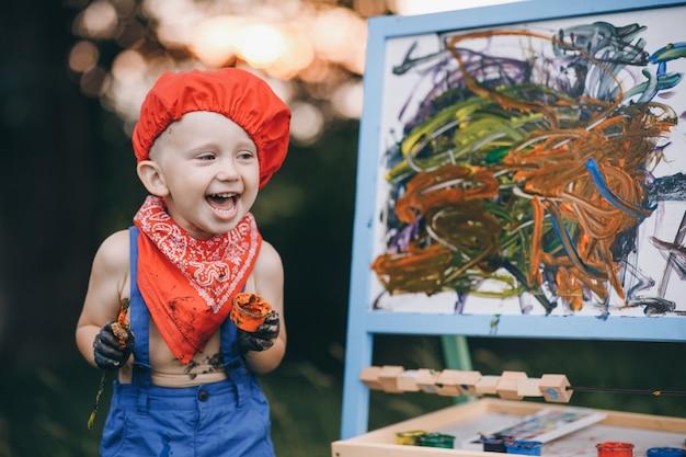 Feche de menino de pintor de sorriso. as mãos do menino do artista, que pinta uma pintura a óleo sobre a natureza no pôr do sol