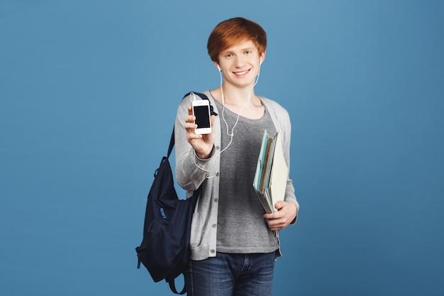 Feche de menino estudante ruivo lindo com mochila sorrindo, segurando muitos cadernos nas mãos, mostrando o telefone celular, ouvindo música favorita em fones de ouvido.
