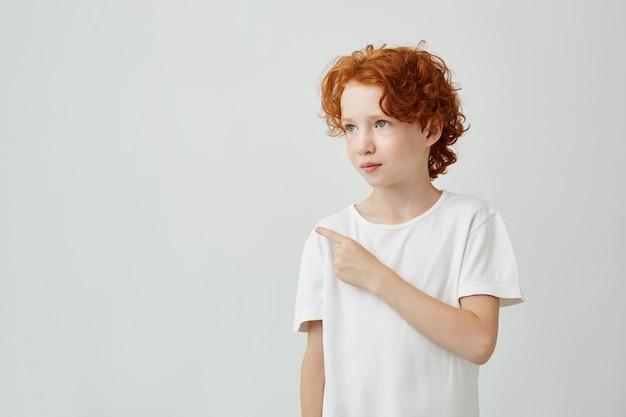 Feche de menino ruivo muito encaracolado com sardas em t-shirt branca, olhando de lado, apontando para a parede branca. copie o espaço.