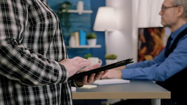 Feche de mensagens de texto de funcionário, enviar e ler mensagens no tablet durante o intervalo em pé no local de trabalho. mulher de negócios usando rede de tecnologia moderna sem fio trabalhando demais à meia-noite