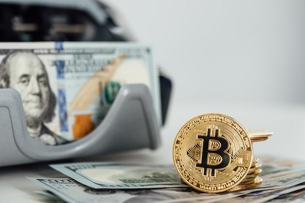 Feche de moedas de criptografia bitcoin e notas de dólar americano. dólares americanos. fundo de dinheiro. moeda de ouro bitcoin cripto-moeda