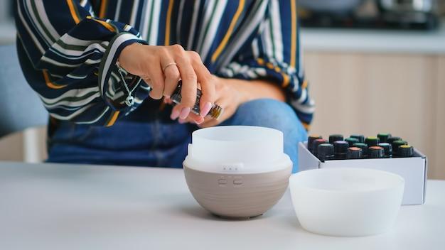 Feche de mulher adicionando óleos essenciais no difusor. aroma saúde essência, bem-estar aromaterapia home spa fragrância tranquiloterapia, vapor terapêutico, tratamento de saúde mental