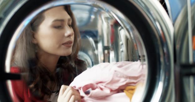 Feche de mulher bonita caucasiana, abrindo a máquina de lavar e tirar roupas limpas após a lavagem. moça à moda bonita que apresenta a roupa na lavanderia pública