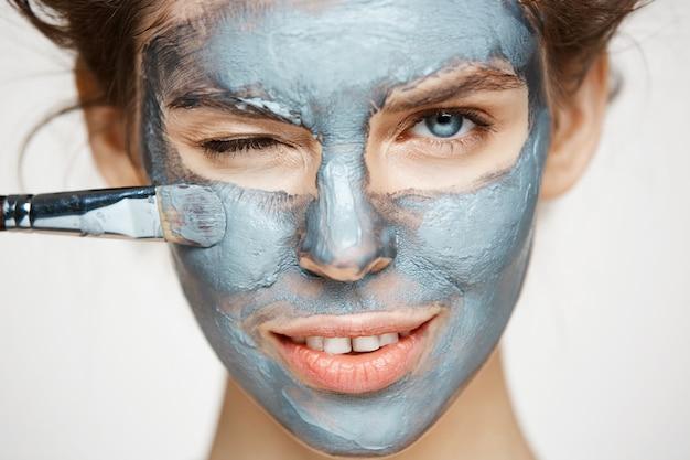 Feche de mulher bonita em rolos de cabelo sorrindo piscando cobrindo o rosto com mack. tratamento facial. cosmetologia de beleza e spa.