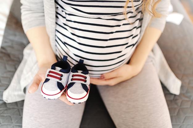 Feche de mulher caucasiana grávida segurando sapatos de bebê e tocando a barriga.