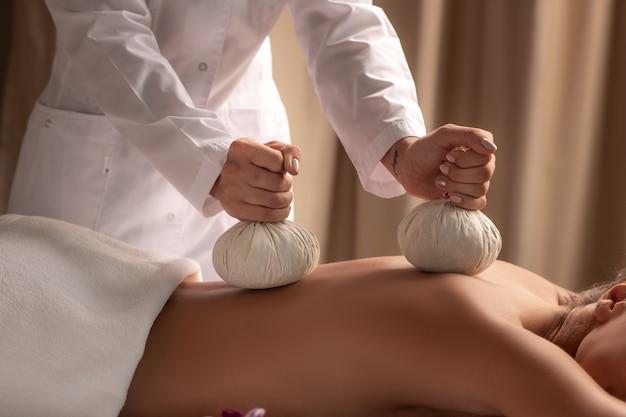 Feche de mulher durante bolas massagem no salão spa.