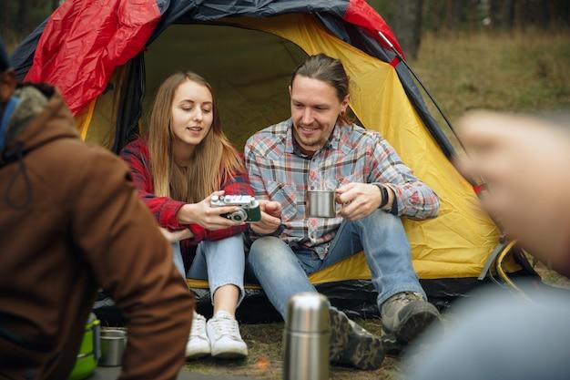 Feche de mulher e homem bebendo chá com um grupo de amigos em um fundo de acampamento na floresta. ter pausa na floresta, conversando, rindo. atividade de lazer, amizade, fim de semana.