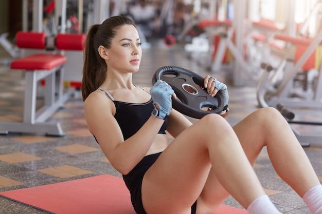 Feche de mulher fazendo exercícios abdominais com placa de peso enquanto está sentado na esteira de esporte no chão do ginásio. vista lateral, desportiva menina veste uniforme preto elegante, com ponitail. conceito de estilo de vida saudável.
