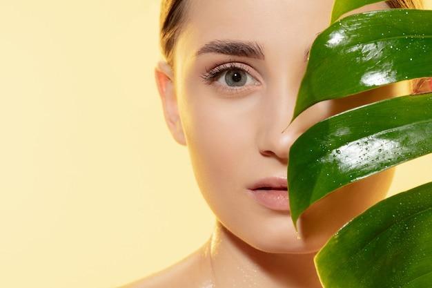 Feche de mulher jovem e bonita com folhas verdes sobre fundo branco. conceito de cosméticos, maquiagem, tratamento natural e ecológico, cuidados com a pele. pele brilhante e saudável, moda, saúde.