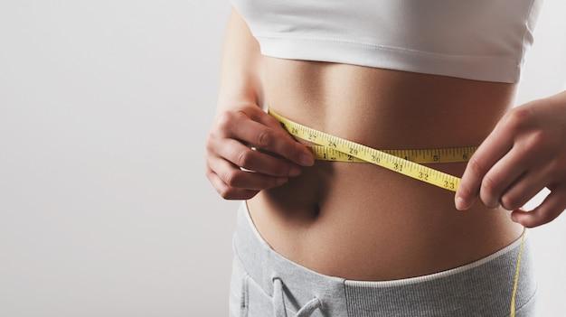 Feche de mulher magro, medindo o tamanho da cintura com fita métrica.