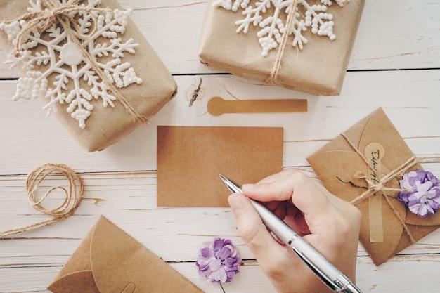 Feche de mulher mãos escrevendo wishlist vazio e cartão de natal na mesa de madeira com decoração de natal.