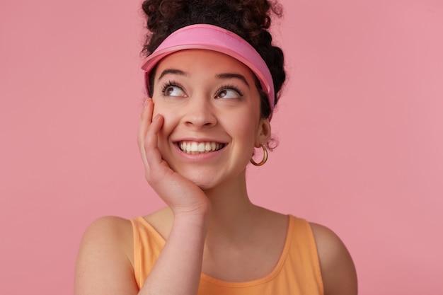 Feche de mulher sonhando com coque de cabelo encaracolado escuro. usando viseira rosa, brincos, top laranja. segura a palma da mão sob o queixo