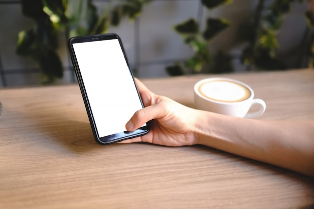 Feche de mulher usando produtos de ordem de celular em branco para fazer compras on-line dentro do café.