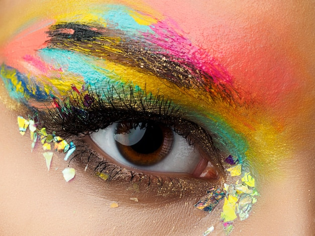 Feche de olhos de mulher azul com um belo marrom com maquiagem de olhos esfumados de tons de vermelho e laranja. a moda moderna compõe.