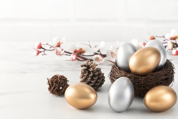 Feche de ovos de páscoa de ouro e prata no ninho com flor de ameixa branca no fundo da mesa de madeira branca brilhante.