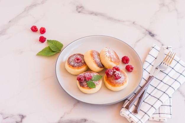 Feche de panquecas de queijo cottage com frutas frescas na mesa de mármore branco. comida saborosa para o café da manhã. syrniki