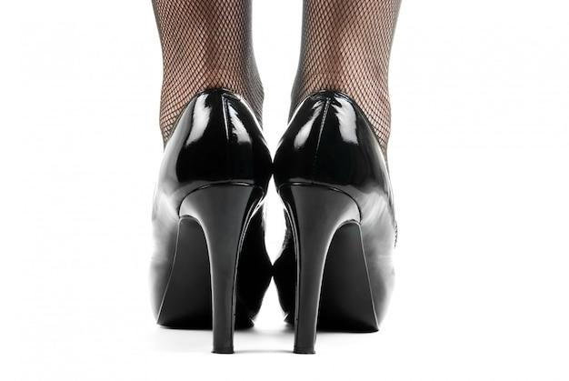 Feche de perna de mulher em sapatos pretos. vista traseira.