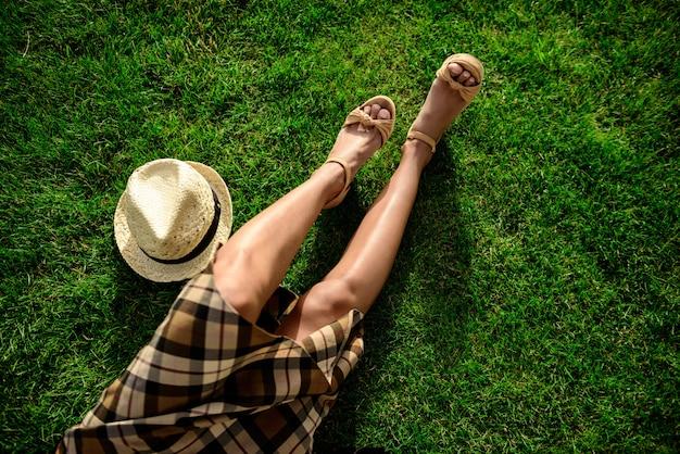 Feche de pernas da menina e chapéu deitado na grama.