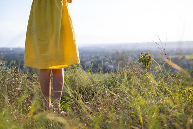 Feche de pernas de mulher jovem com vestido de verão amarelo em pé no campo gramado ao ar livre.