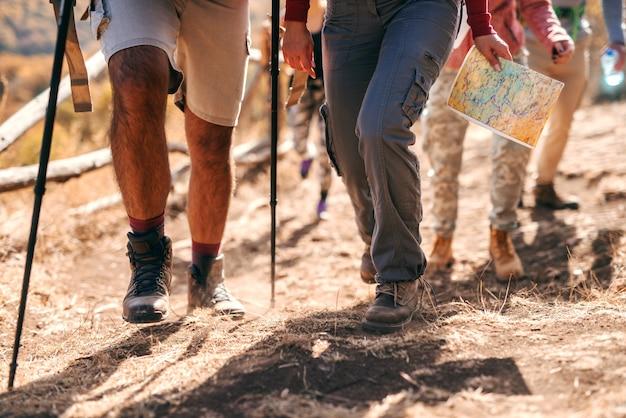 Feche de pernas dos caminhantes subindo na montanha. tempo de outono.