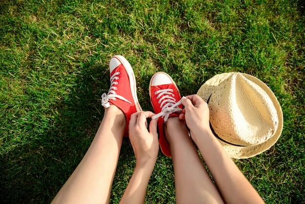 Feche de pernas em keds vermelhos, deitado na grama.