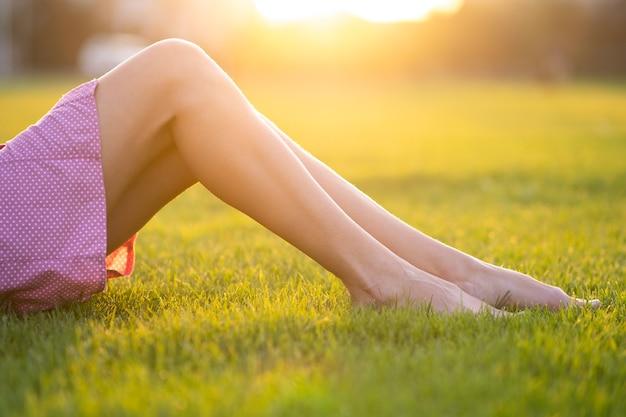 Feche de pernas finas femininas, descansando na grama verde num dia quente de verão.