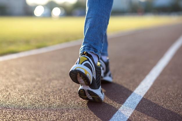Feche de pés de mulher no esporte tênis e jeans azul na pista de corrida na quadra de esportes ao ar livre.