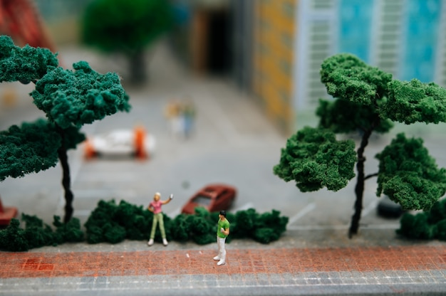 Feche de pessoas pequenas ou modelo de pessoas andando no parque.