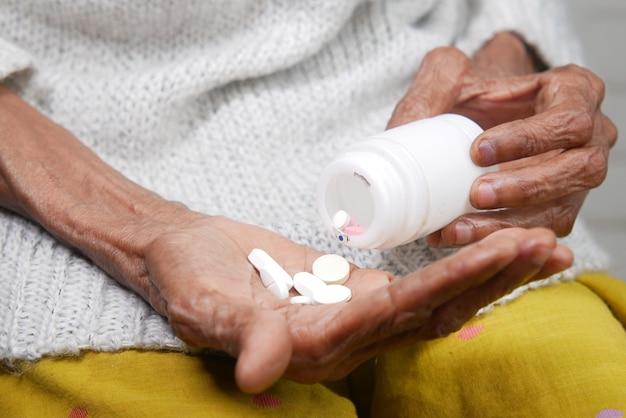 Feche de pílulas e cápsulas na mão de mulher sênior