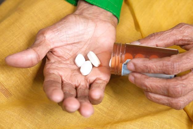 Feche de pílulas e cápsulas na mão de mulheres sênior
