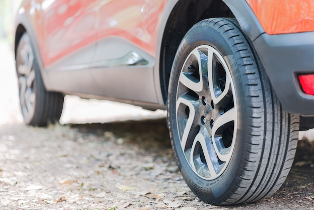Feche de pneus de carro. vista traseira de um carro estacionado sobre uma estrada coberta com as folhas de outono.