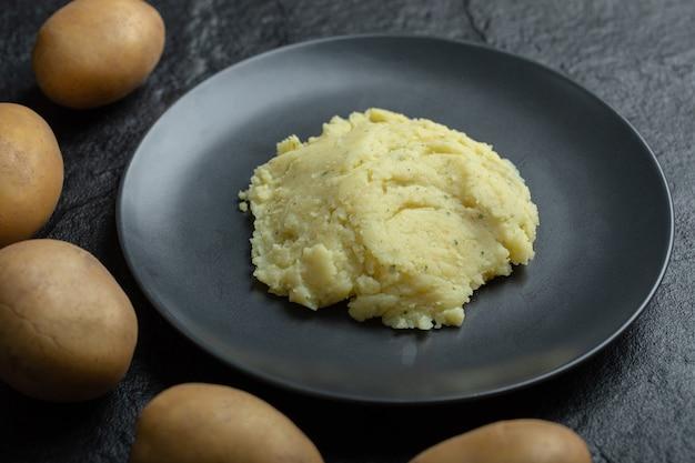 Feche de purê de batata em um prato e batatas frescas em torno dele.