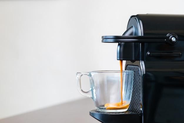 Feche de refrescante espresso derramando da máquina de cápsulas em uma xícara em casa.