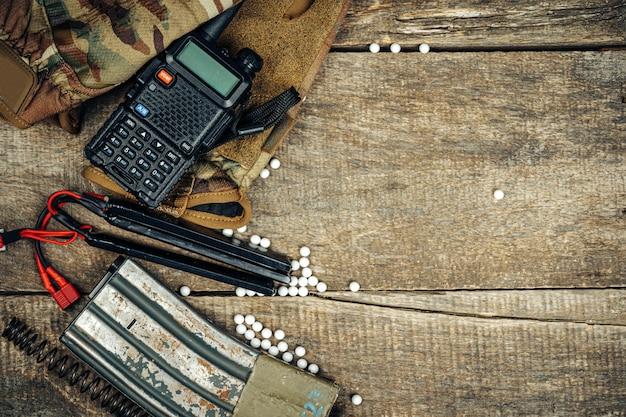 Feche de revista de armas de airsoft e bolas de airsoft em fundo de madeira