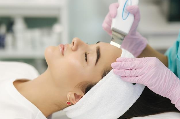 Feche de rosto feminino com pele macia. mulher na clínica de cosmetologia fazendo um procedimento de beleza para